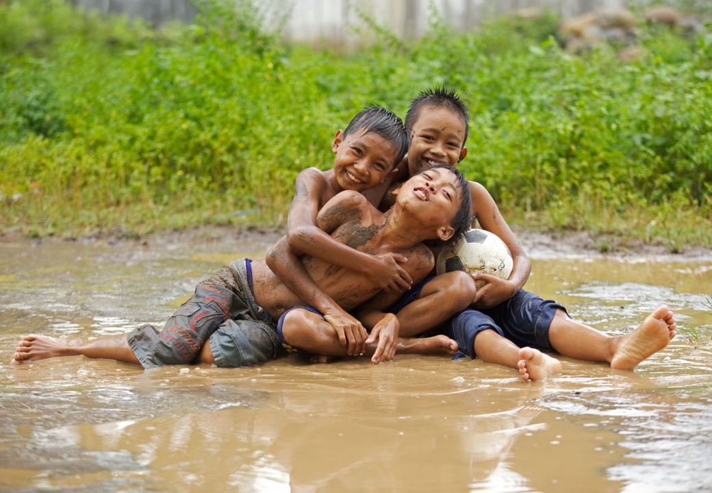 Three young boys playing in a mud after the rain , East Java , Indonesia